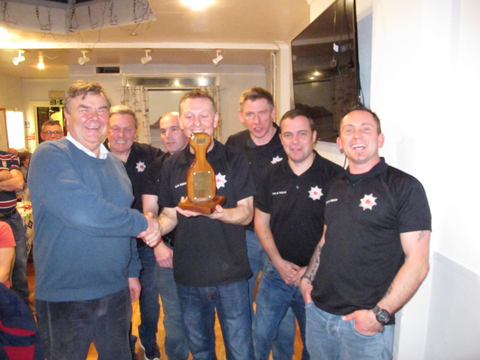 Bob Gilbert, RNLI Chairman of Fundraising, hands the trophy to the victorious volunteers from the Dartmouth Fire station.