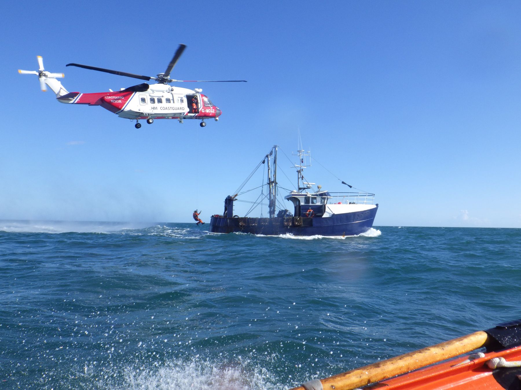 The Coastguard paramedic is winched aboard the fishing boat.
