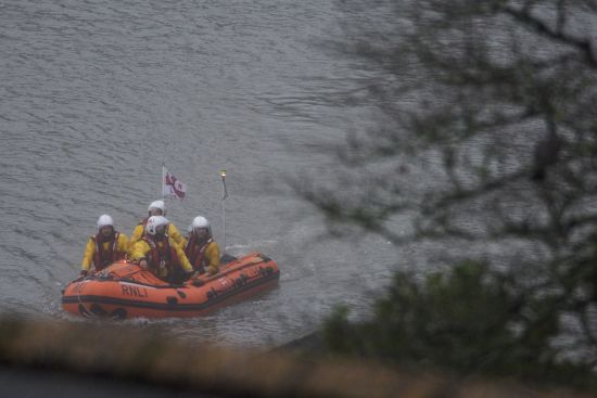 RNLI Dart inshore lifeboat searching the river bank